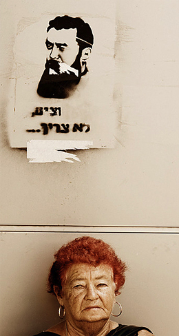 Mujer israelí junto a un graffiti del busto de Theodor Herzl