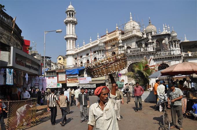 Templos suntuosos y pequeños comerciantes en una calle de Mumbai